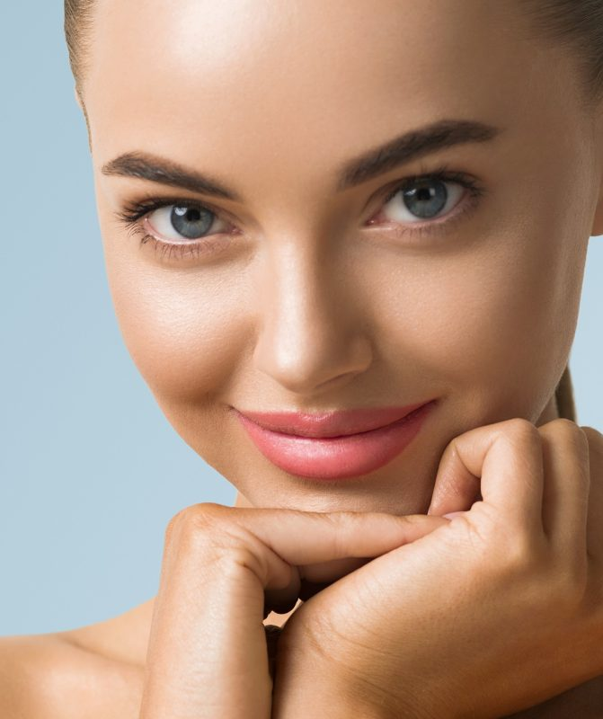 Clean skin woman face macro skin beauty tanned face beautiful smile over blue background